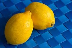 Deux citrons sur le fond bleu tissé de tapis avec l'espace de copie Photographie stock libre de droits