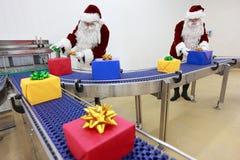 Deux clauses de Santa fonctionnant à la chaîne de production Images stock