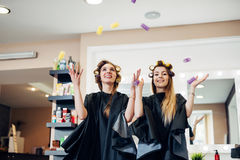 Deux clients féminins de salon de beauté se tenant dans des rouleaux de cheveux ayant l'amusement jouant rire Photographie stock libre de droits