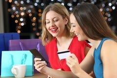 Deux clients faisant des emplettes sur la ligne avec la carte de crédit Image libre de droits