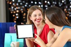 Deux clients montrant un écran de comprimé pendant la nuit Image stock