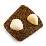 Deux clous de girofle d'ail sur une partie de pain noir Photo libre de droits