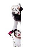 Deux clowns dans l'amour regardant autour d'une frontière Photographie stock