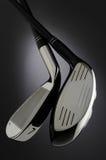 Deux clubs de golf sur le fond foncé Images stock