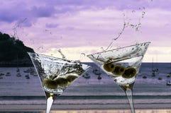 Deux cocktails avec éclabousser martini et olives sur un beac de coucher du soleil image stock