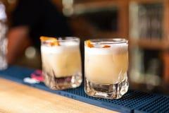 Deux cocktails oranges avec la peau d'orange sur la barre Photos stock