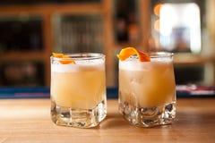 Deux cocktails oranges avec la peau d'orange sur la barre Photos libres de droits