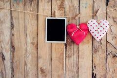 Deux coeur et photo encadrent accrocher sur la corde de corde à linge avec le woode Images libres de droits