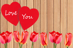 Deux coeur et tulipes rouges au-dessus de texture en bois Image stock