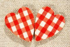 Deux coeurs à carreaux rouges d'amour sur le fond de toile de jute. Images libres de droits