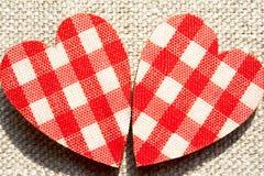 Deux coeurs à carreaux rouges d'amour sur le fond de toile de jute. Photo stock