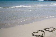 Deux coeurs écrits sur le sable photo stock