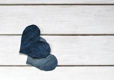 Deux coeurs élégants sont coupés du denim bleu se trouvant ensemble sur le wh Photographie stock libre de droits
