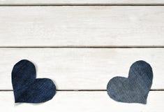 Deux coeurs élégants sont coupés du tissu bleu de denim se trouvant sur un wh Image libre de droits