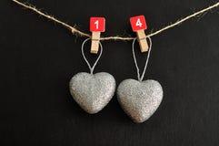 Deux coeurs argentés accrochant sur une corde Photos libres de droits