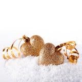 Deux coeurs avec des bandes d'or sur la neige Photo stock