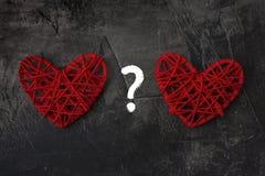 Deux coeurs avec un point d'interrogation sur un fond foncé Thème pour le jour et le mariage du ` s de St Valentine Images libres de droits