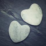 Deux coeurs blancs de zen ont formé la roche sur une tuile Photo libre de droits