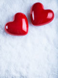 Deux coeurs brillants rouges sur un fond blanc givré de neige Concept d'amour et de St Valentine Photographie stock