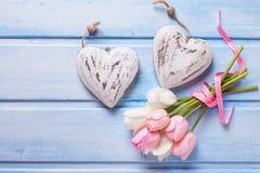 Deux coeurs décoratifs et tulipes blanches et roses tendres o de ressort Photographie stock