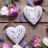 Deux coeurs décoratifs et tulipes lumineuses fleurit sur âgé texturisé Image stock