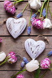 Deux coeurs décoratifs et tulipes lumineuses fleurit sur âgé texturisé Photographie stock