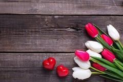 Deux coeurs décoratifs rouges et tulipes lumineuses de ressort fleurit Image stock