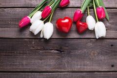 Deux coeurs décoratifs rouges et tulipes lumineuses de ressort fleurit dessus Image libre de droits
