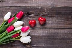 Deux coeurs décoratifs rouges et tulipes lumineuses de ressort fleurit dessus Images stock