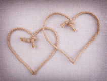 Deux coeurs d'amour faits en chaîne de caractères croisée ensemble Photographie stock