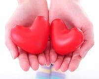 Deux coeurs dans des mains femelles Photographie stock