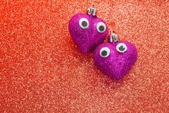 Deux coeurs dans l'amour avec les yeux ouverts dans la texture rouge Image libre de droits