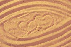Deux coeurs dans le sable sur la plage Symboll d'amour Photographie stock
