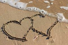 Deux coeurs dans le sable sur la plage Vagues avec la mer bleue o de mousse Image libre de droits