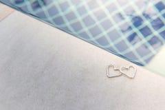Deux coeurs de boucle d'oreille sur la piscine Photo libre de droits