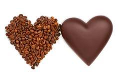 Deux coeurs de chocolat et des grains de café sur le fond blanc Photos stock