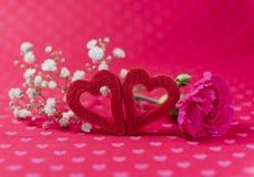 Deux coeurs de feutre avec l'oeillet et fleurs blanches sur le hea romantique Photographie stock libre de droits