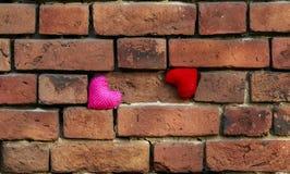Deux coeurs de knit rouges et roses se tiennent sur un vieux rouge de émiettage Photographie stock