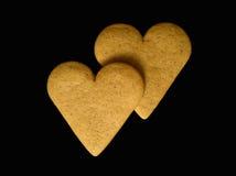 Deux coeurs de pain d'épice d'isolement sur un backgro noir Photographie stock