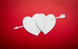 Deux coeurs de papier percés avec un symbole de flèche pour le jour de Valentines Photos stock
