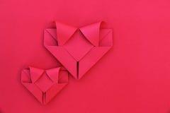 deux coeurs de papier rouges fois sur le rouge pour le modèle et le fond Images libres de droits
