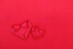 deux coeurs de papier rouges fois sur le rouge pour le modèle et le fond Image libre de droits