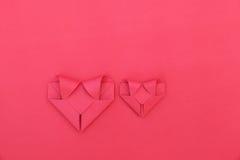 deux coeurs de papier rouges fois sur le rouge pour le modèle et le fond Photo stock