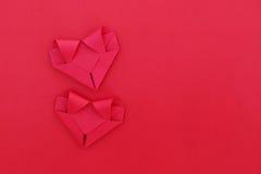 deux coeurs de papier rouges fois sur le rouge pour le modèle et le fond Photo libre de droits