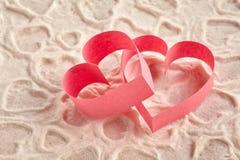 Deux coeurs de papier rouges sensibles sur la dentelle modelée Images libres de droits