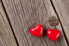 Deux coeurs de sucrerie au-dessus de bois Images stock
