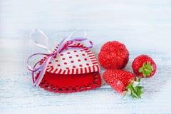 Deux coeurs de tissu avec le cadeau mûr de fraises pour le jour du ` s de Valentine sur un fond en bois bleu Photos stock