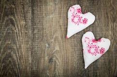 Deux coeurs de tissu sur le plancher en bois brun Images stock