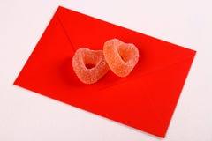 Deux coeurs des sucreries de sucre sur la lettre d'amour rouge Photo libre de droits