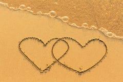 Deux coeurs dessinés dans le sable de mer avec la vague molle Amour Images stock